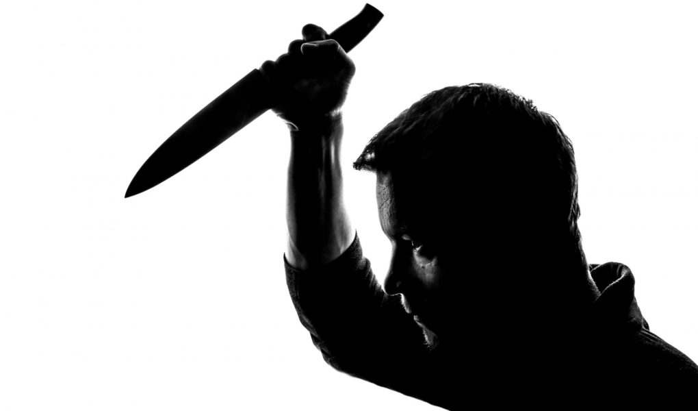 Silhouette of man holding a knife above his head